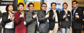 Representatives from NAS, ADK, and Konami at MIPTV 2011 celebrating launch of Yu-Gi-Oh! ZEXAL