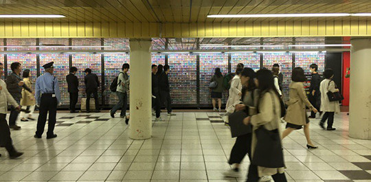Commuters passing by the Yu-Gi-Oh! The Dark Side of Dimensions card exhibit in Shinjuku