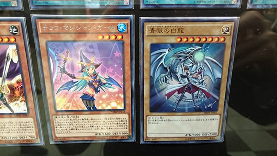 Choco Magician Girl and Blue-Eyes White Dragon cards at the Yu-Gi-Oh! The Dark Side of Dimensions card exhibit in Shinjuku
