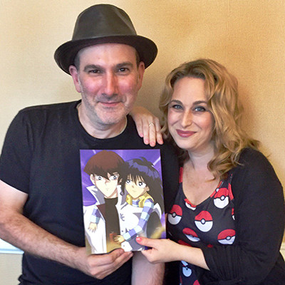 Eric Stuart and Tara Sands holding fan art of Kaiba and Mokuba at AkaiCon 2016