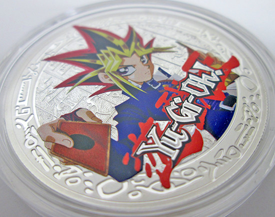 Close-up of the Yami Yugi coin in its plastic case