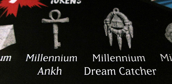 The Millennium Ankh and Millennium Dream Catcher highlighted on the back of the USAopoly Yu-Gi-Oh! Monopoly box