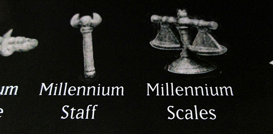 The Millennium Staff and Millennium Scales highlighted on the back of the USAopoly Yu-Gi-Oh! Monopoly box
