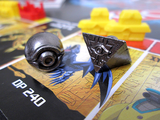 Close-up of the Millennium Eye and Puzzle tokens on the USAopoly Yu-Gi-Oh! Monopoly board
