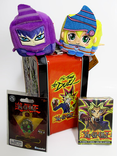 Side view of Aquarius' Yu-Gi-Oh! lunch box, Dark Magician and Dark Magician Girl Kawaii Cubes, a Kuriboh pin by Grin Studios, and Yu-Gi-Oh! playing cards by Aquarius
