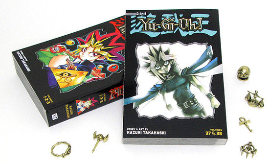VIZ Media's Yu-Gi-Oh! 3-in-1 Edition, volumes 1 and 13, surrounded by some Millennium Items