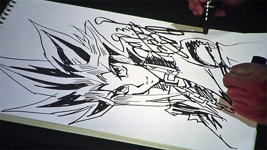 Kazuki Takahashi signing his name on his completed illustration of Yugi at his live drawing session at MAGIC 2019