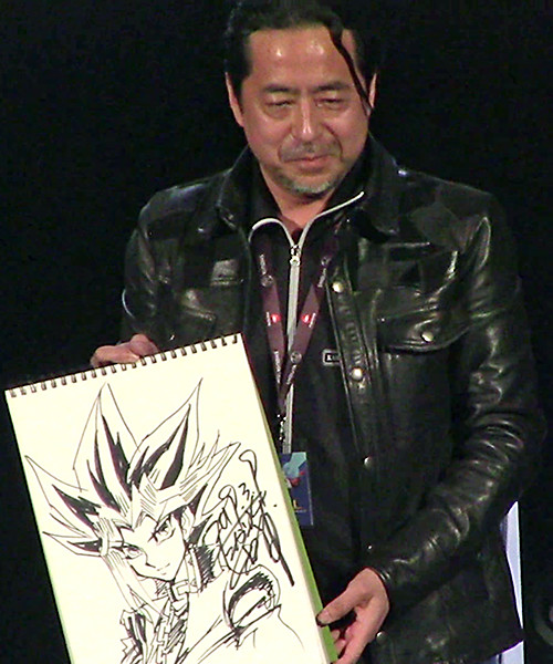 Close-up of Kazuki Takahashi posing with his illustration of Yugi at his live drawing session at MAGIC 2019