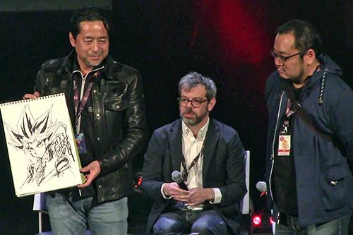 Kazuki Takahashi posing with his illustration of Yugi at his live drawing session at MAGIC 2019, with Matthieu Pinon and Naoki Kawashima