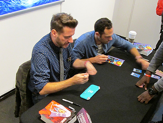 Darren Dunstan and Jake Paque signing autographs at the Yu-Gi-Oh! Tribute Art Show NYC
