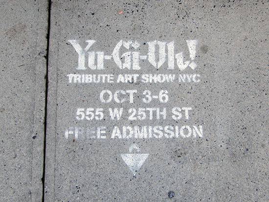 Spray-painted sign advertising the Yu-Gi-Oh! Tribute Art Show NYC on the pavement