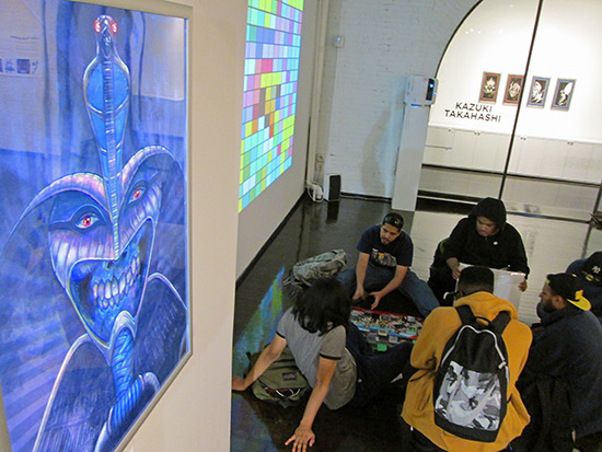 A Yu-Gi-Oh! duel taking place near Michael Vincent Bramley's Forbidden piece at the Yu-Gi-Oh! Tribute Art Show NYC