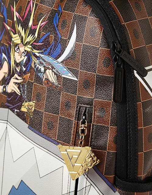 Close-up of Sprayground's Yu-Gi-Oh! Duel Disk backpack showing the Millennium Puzzle