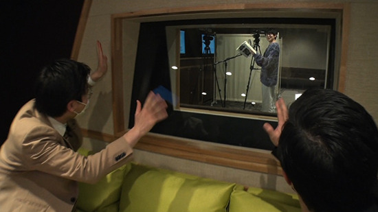 Tokyo Hoteison waving at voice actor Natsuki Hanae, who is in a recording booth