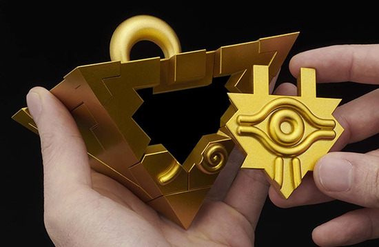 A hand holding the Yu-Gi-Oh! Millennium Puzzle model kit by Bandai